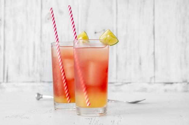 Zwei gläser bay breeze cocktail garniert mit limettenschnitzen auf holzhintergrund