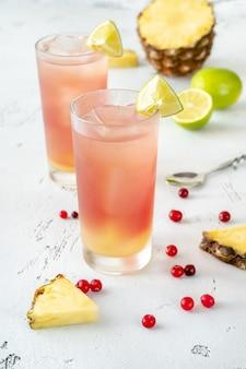 Zwei gläser bay breeze cocktail, garniert mit limettenschnitzen, serviert mit ananasscheiben und frischen preiselbeeren