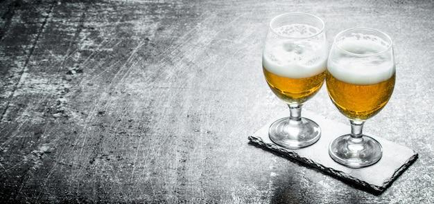 Zwei gläser bier auf einem untersetzer. auf schwarzem rustikalem tisch