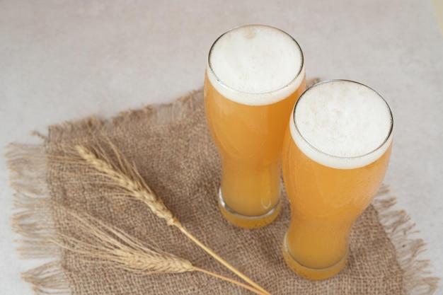 Zwei gläser bier auf sackleinen mit weizen