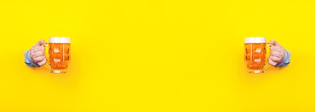 Zwei gläser bier in den händen auf einem gelben