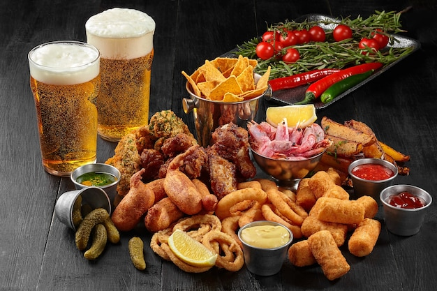 Zwei gläser bier mit herzhaften snacks und gemüse auf schwarz
