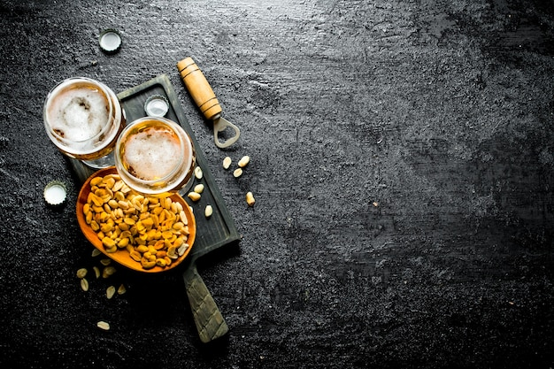 Zwei gläser bier und erdnüsse in einer schüssel auf einem schwarzen schneidebrett. auf schwarzem rustikalem tisch