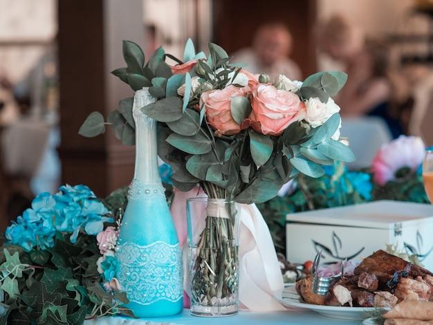 Zwei gläser champagner auf dem hintergrund des hochzeitsblumenstraußes der rosa rosen. weicher fokus, selektiver fokus