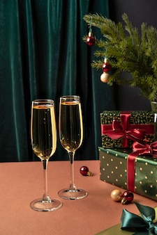 Zwei gläser champagner auf dem tisch mit weihnachtsgeschenk