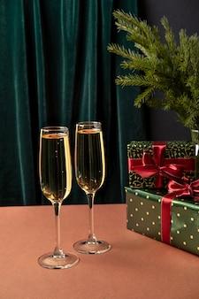 Zwei gläser champagner auf dem tisch mit weihnachtsgeschenken