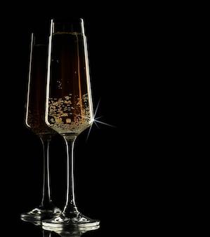 Zwei gläser champagner auf einem schwarzen hintergrund
