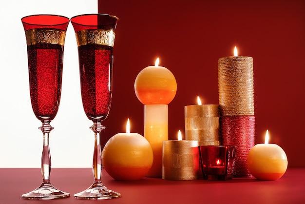 Zwei gläser champagner, brennende kerzen auf rot. konzept für die gestaltung von neujahrskarten und weihnachtsgrüßen.