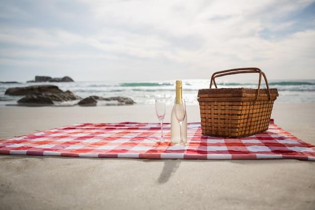 Zwei gläser, champagner-flasche und picknickkorb auf stranddecke