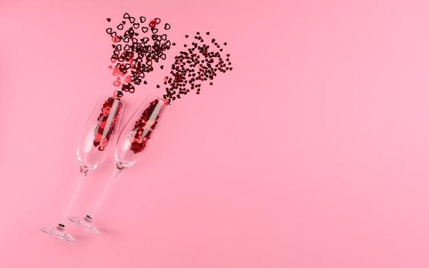 Zwei gläser champagner gefüllt mit herzförmigen pailletten an einem valentinstag des rosa hintergrunds.