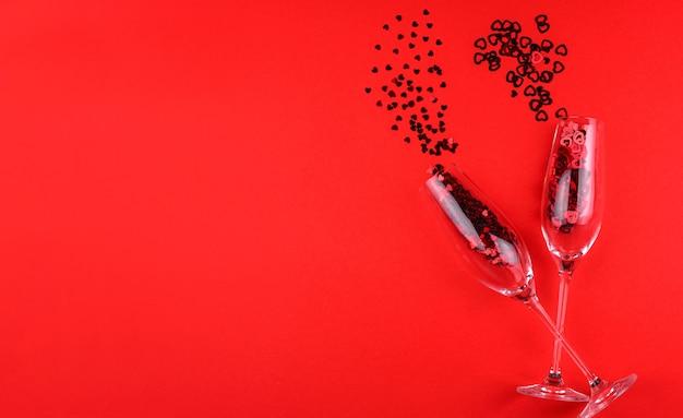 Zwei gläser champagner gefüllt mit herzförmigen pailletten an einem valentinstag des roten hintergrunds.