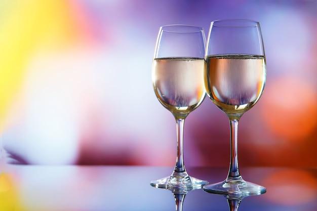 Zwei gläser champagner gegen bunte lichter