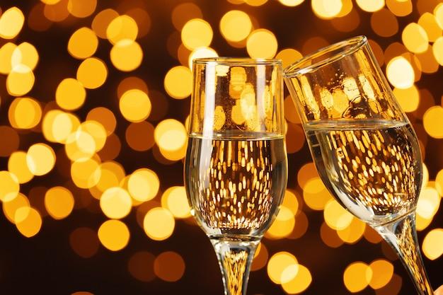 Zwei gläser champagner gegen glänzendes bokeh beleuchtet hintergrund
