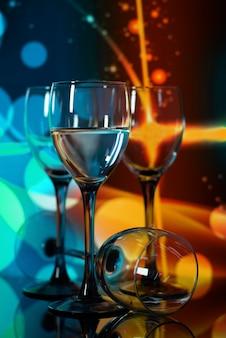 Zwei gläser champagner mit lichtern im hintergrund. sehr geringe schärfentiefe, fokus auf nahes glas.
