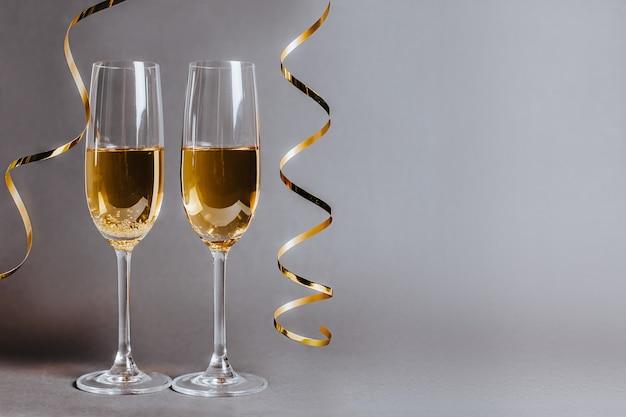 Zwei gläser champagner mit lichtern und bändern auf einem schwarzen grauen hintergrundfeiertag