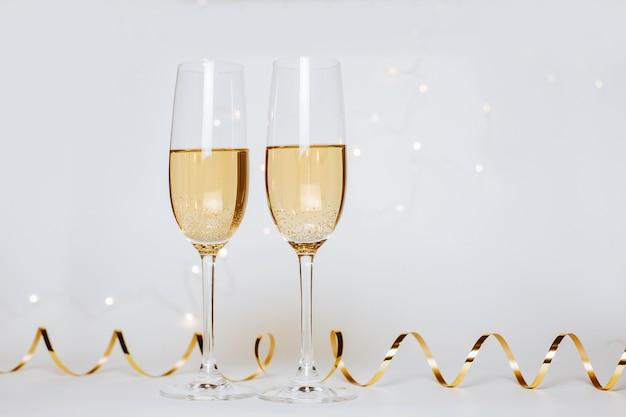 Zwei gläser champagner mit lichtern und bändern