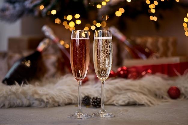 Zwei gläser champagner stehen in der nähe des baumes