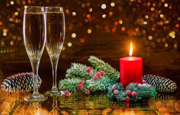 Zwei gläser champagner und eine brennende kerze in einem dekorativen weihnachtskranz aus fichtenzweigen auf einer dunkelheit