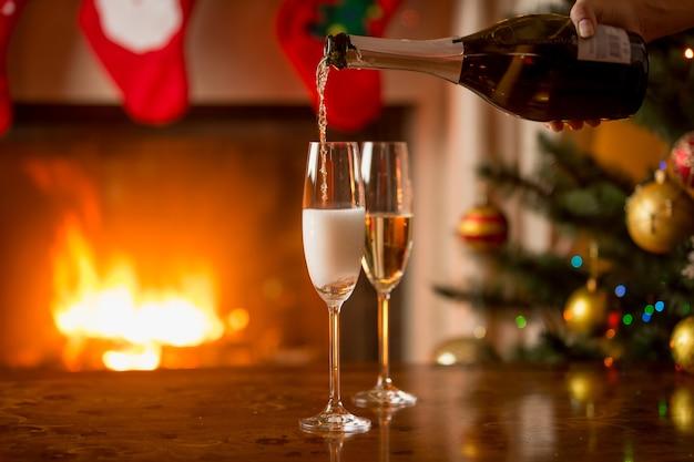 Zwei gläser champagner werden aus der flasche gefüllt