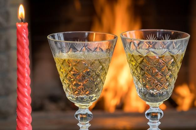 Zwei gläser champagnerwein und eine kerze vor dem gemütlichen kamin, im landhaus, winterferien.