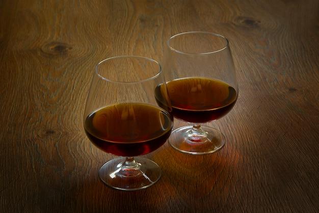 Zwei gläser cognac auf holztisch