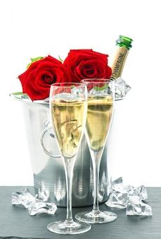 Zwei gläser, eine flasche champagner und rote rosen