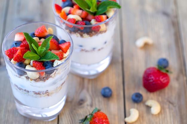Zwei gläser erdbeerparfait aus frischem obst, joghurt, blaubeeren, leinsamen und müsli auf einem hölzernen hintergrund.