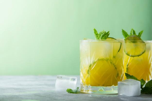 Zwei gläser erfrischende getränke mit eiswürfeln, saft und limettenfrucht, partycocktail. platz kopieren