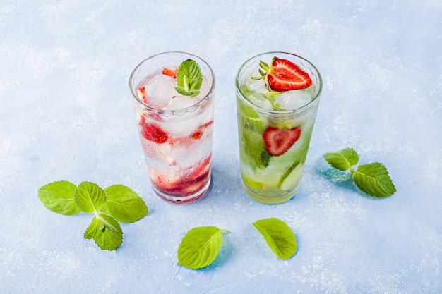 Zwei gläser erfrischendes kühles entgiftungsgetränk mit erdbeere, limette und minze. verschiedene sommerlimonaden oder eistee. mojito-cocktail mit eiswürfeln. gesundes essen.