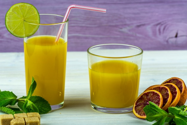 Zwei gläser frischer orangensaft. minzzweige und orangenscheiben