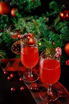 Zwei gläser frisches cranberry-getränk mit weihnachtsverzierung. neujahrstabelle.