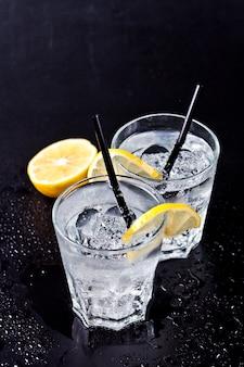 Zwei gläser frisches kaltes tafelwasser mit eiswürfeln und zitronenscheiben