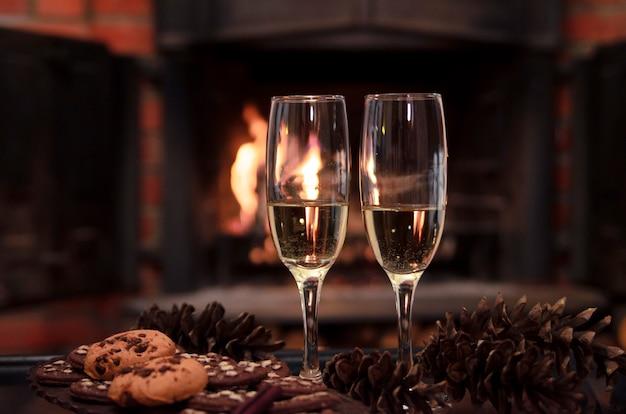 Zwei gläser funkelnder goldener champagner gegen kamin mit flamme