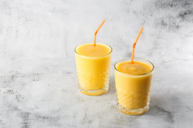 Zwei gläser gelbe bananen-, orangen-, mango-smoothies oder saftfrucht lokalisiert auf hellem marmorhintergrund. draufsicht, speicherplatz kopieren. werbung für cafe-menü. horizontales foto.