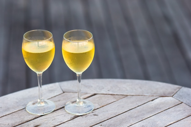 Zwei gläser geschmackvoller weißwein bei sonnenuntergang auf holztisch
