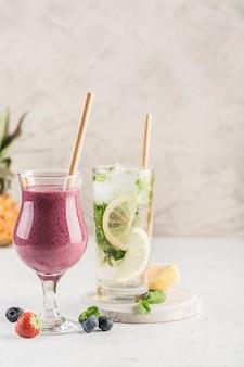 Zwei gläser getränke, ein smoothie aus frischen beeren und ein mojito mit zitrone und minze auf hellem hintergrund. seitenansicht mit copyspace. restaurant essen.