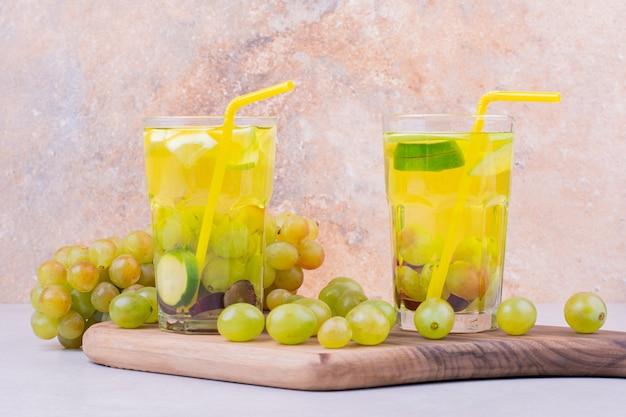 Zwei gläser grüner traubensaft auf einem holzbrett