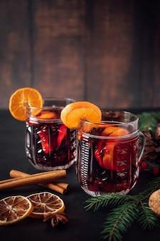 Zwei gläser heißer glühwein mit früchten und gewürzen auf einem dunklen hintergrund. winterwärmendes urlaubsgetränk.