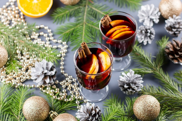Zwei gläser heißer glühwein mit gewürzen und orangenscheiben. weihnachtsgetränk mit kerze und dekorationen. draufsicht
