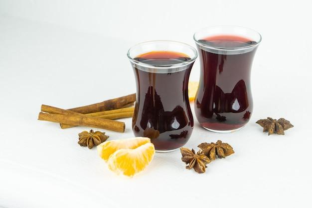 Zwei gläser heißer rotwein mit mandarinenscheiben, zimt und anissternen