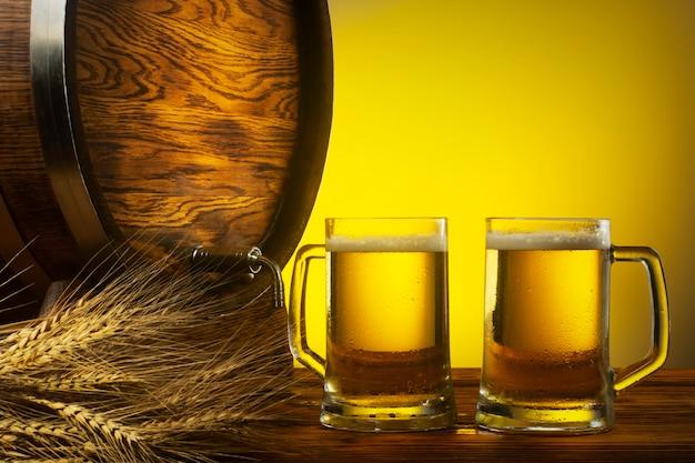Zwei gläser helles bier, ein eichenfass und ein bündel gerste freier platz für eine inschrift