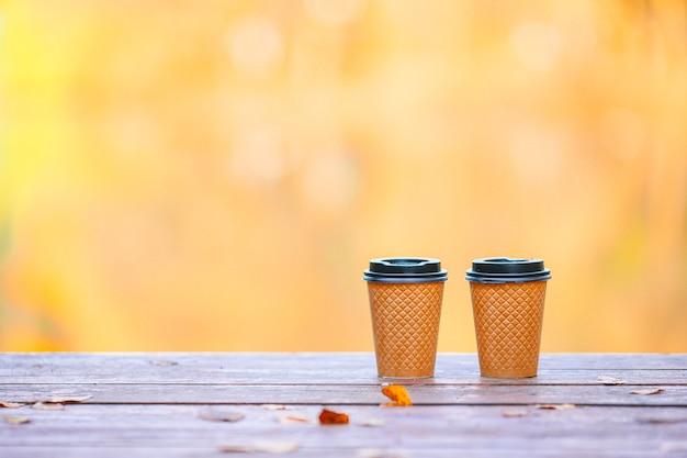 Zwei gläser kaffee zum mitnehmen auf einem hölzernen pier am see an einem herbsttag
