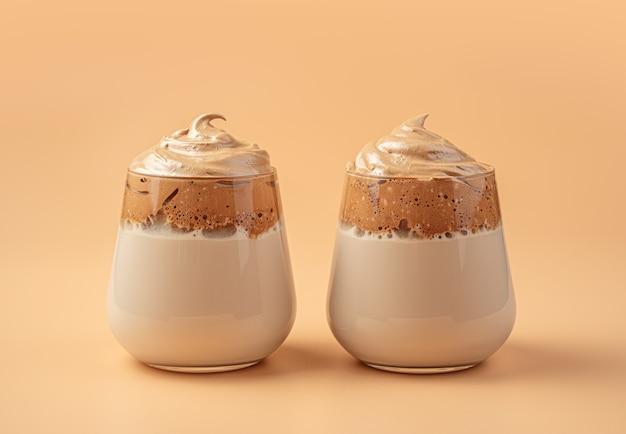Zwei gläser kaffeegetränk mit milch und schlagschaum an einer orangefarbenen wand