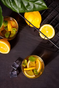Zwei gläser kalter erfrischungstee mit eis und zitronenfrüchten.