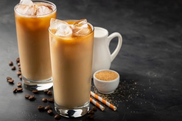 Zwei gläser kalter kaffee auf einem dunklen hintergrund.