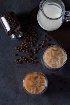 Zwei gläser kalter kaffee mit eiswürfeln, kaffeebohnen und krug milch auf dunklem hintergrund, ansicht von oben