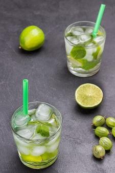 Zwei gläser kaltes getränk mit kalk, minze und eis. stroh im glas. limettenscheiben und stachelbeeren auf dem tisch. schwarzer hintergrund. ansicht von oben