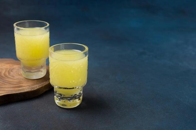 Zwei gläser köstlicher limoncello mit einem ständer auf blauem hintergrund