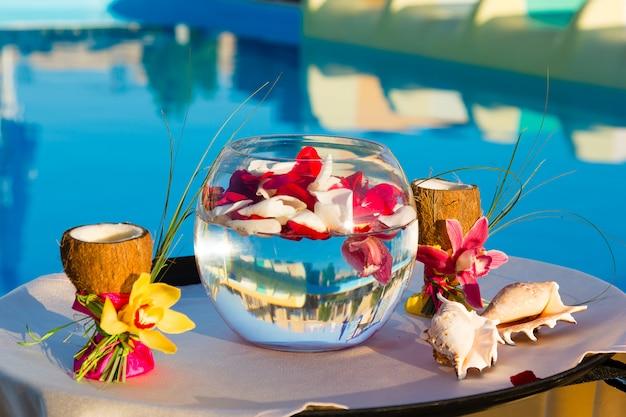 Zwei gläser kokosnuss mit orchideen, zwei muscheln und rosenblüten in einem goldfischglas