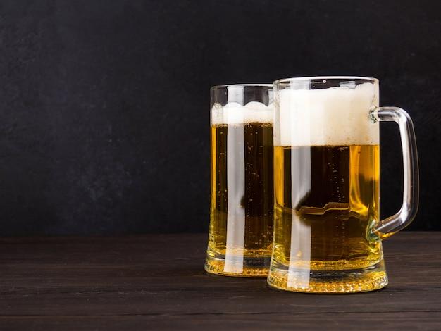 Zwei gläser lager serviert auf alten holzbrettern